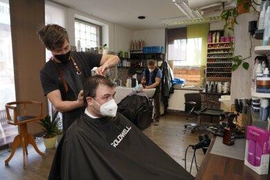 Am Montag im Salon Tiepmar in Rodewisch: Inhaber Jörg Tiepmar frisiert Oliver Buchhold, im Hintergrund kümmert sich Joachim Tiepmar um Marlene Hutschreuther.