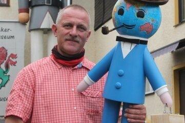 Museumsinhaber Uwe Löschner zeigt seinen neuesten Nussknacker-Zuwachs. Konstrukteur Frank Müller musste das knackfähige Messemännchen so gestalten, dass die Figur quasi mit dem Hals knackt - zumal der Kopf ja den Globus darstellt.