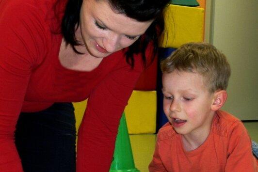 Ergotherapeutin Jenny Morgenstern von der Frühförder- und Beratungsstelle des Diakonischen Werks Rochlitz in der Arbeit mit einem Jungen mit Förderbedarf. Das Bild ist vor der Coronapandemie entstanden.