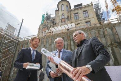 Baubürgermeister Michael Stötzer, Bauherr Siegfried Weishaupt und Architekt Claus Höhn (von links) füllen die sogenannte Zeitkapsel, die anschließend im Grundstein für den Neubau neben der Villa Zimmermann versenkt wird, mit Plänen, Tageszeitungen und weiteren Zeitdokumenten.