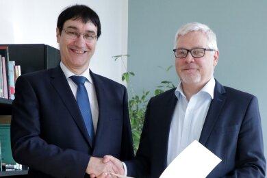 Der neue Rektor der WHZ, Stephan Kassel (l.), erhält seine Bestellungsurkunde aus den Händen von Staatssekretär Uwe Gaul (r.)