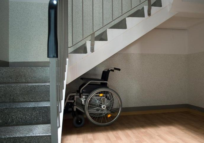Ein Rollstuhl steht unter einer Treppe in einem Wohnhaus in Sachsen.