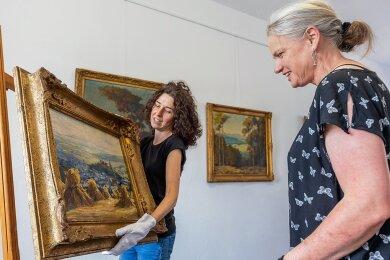 Museumsmitarbeiterin Nadine Holesch (links), und Museumsleiterin Sina Lorbeer-Klausnitz richten das Bild von Otto Eduard Pippel aus, dessen Kauf durch Spenden finanziert wurde.