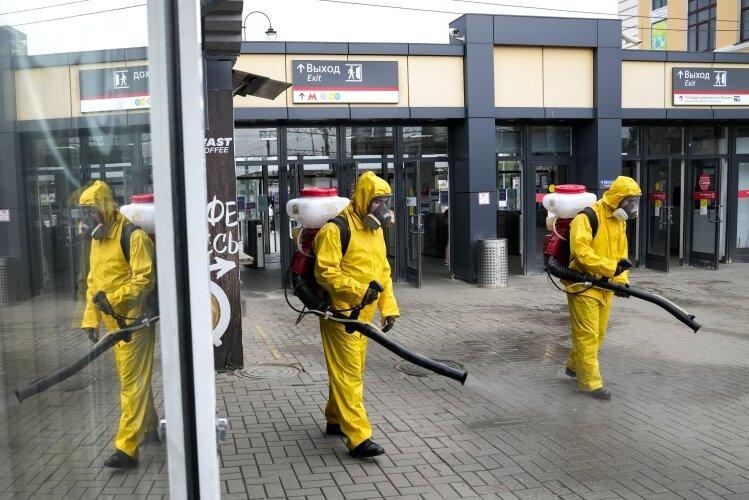 Mitarbeiter des Katastrophenschutzes desinfizieren einen Bahnsteig des Sawjolowski-Bahnhofs in Moskau.