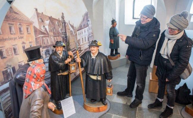 Matthias und Rita Weiß aus Gelenau betrachten in der Bergkirche in Annaberg-Buchholz die neu angeordneten Figuren der Bergmännischen Krippe vor den neu gestalteten Leinwänden. Hier sind Marktfrau, Ratsherr und Nachtwächter vor der historischen Marktkulisse im Gespräch.