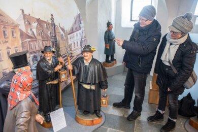 Blick in die Bergkirche in Annaberg-Buchholz: Hier sind die Figuren von Marktfrau, Ratsherr und Nachtwächter vor der historischen Marktkulisse im Gespräch.