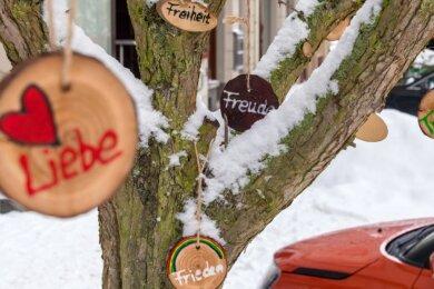 Als Symbol für Hoffnung und Gemeinsamkeit hat eine Olbernhauerin rund 100 hölzerne Baumhänger in der Olbernhauer Innenstadt verteilt.