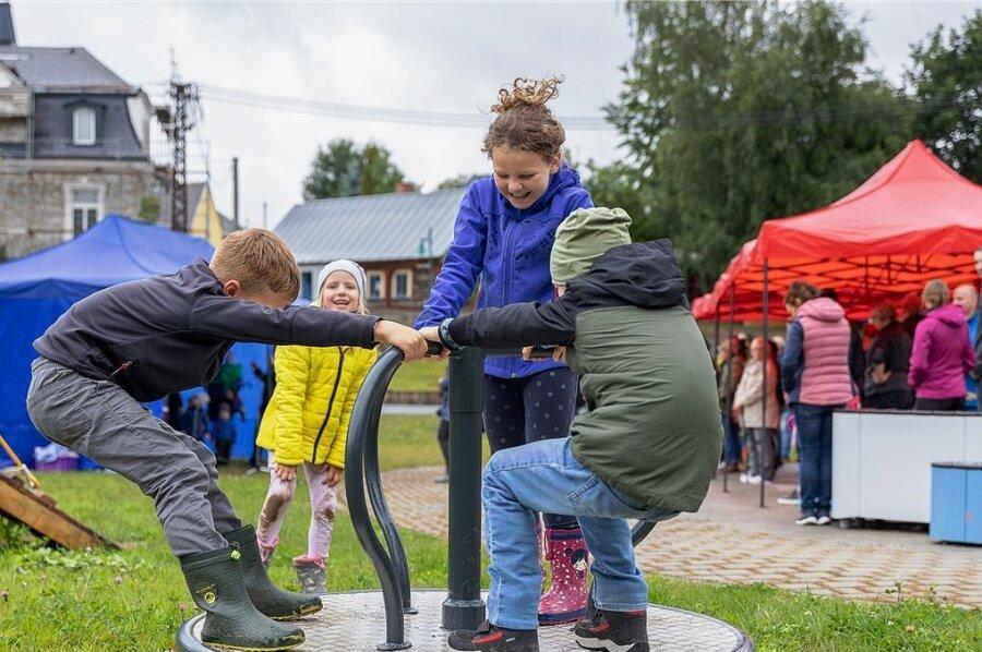 Johanna, Elenor, Finn und Max hatten bei der kleinen Einweihungsfeier viel Spaß auf einem der Spielgeräte auf dem neuen Dorfplatz. In der Bildmitte das Umgebindehaus, in das die Festgesellschaft später einrückte, rechts die modernen Sitzgelegenheiten.