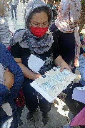 Eine Frau aus Afghanistan zeigt die Ausweispapiere ihrer Familie. Der blaue Stempel der griechischen Behörden bedeutet: Sie wurden als Asylbewerber anerkannt. Damit beginnen oft neue Schwierigkeiten.