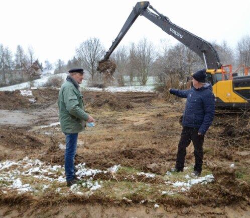 Wird seit dieser Woche entschlämmt: der Katzenteich im Treuener Ortsteil Pfaffengrün. Gerhard Jacobi und Volkmar Schwarz (v. l.) vom Ortschaftsrat sind froh, dass das Biotop auf Vordermann gebracht wird.