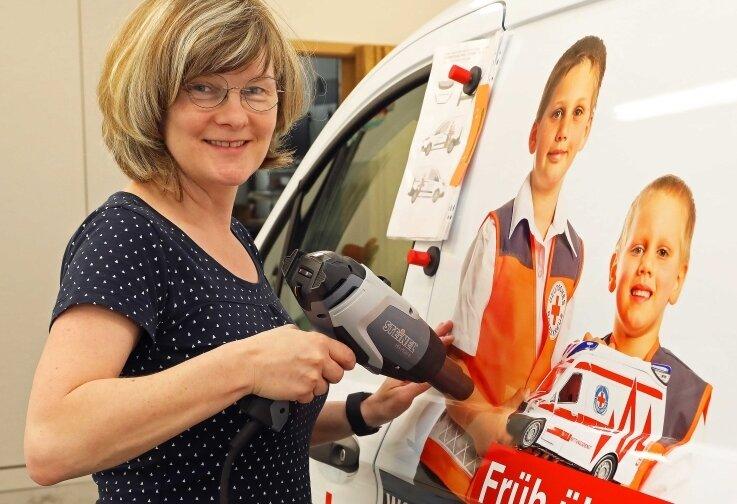 Cathleen Schloske von der Werbemanufaktur beim Bekleben der Fahrzeuge.