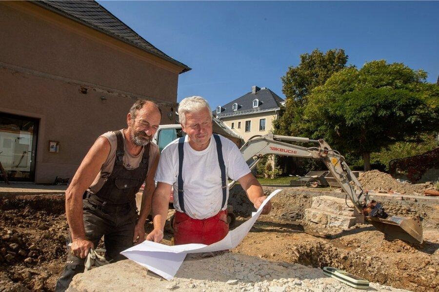 Das Gelände des Pfarrhofs stellt für den Bau der Sternwarte eine Herausforderung dar. Nach dem Abriss dreier Garagen klafft vorerst das Loch einer Baugrube. Gemeindearbeiter Dietmar Rohloff (links) und Uwe Habermas vom Baugeschäft Müller aus Thalheim im Erzgebirge schauen, was geht.