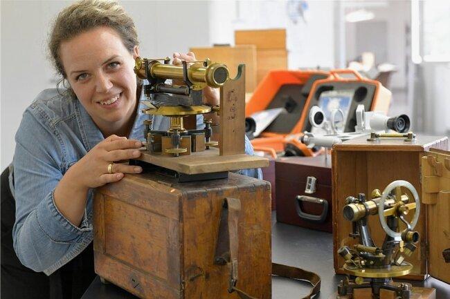 Nadja Lebsuch-Niachos leitet die Montage in der FPM Holding GmbH. Hier prüft sie ein Nivelliergerät von Hildebrand aus der Zeit um 1900. Rechts im Bild ein Theodolit von Lingke von vor 1900. Die historischen Geräte sind in einer Sonderausstellung im Stadt- und Bergbaumuseum zu sehen.