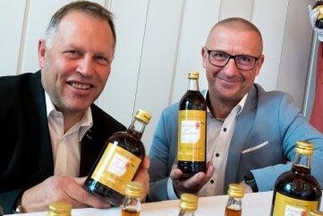 Oberbürgermeister André Heinrich (rechts) und Jens Sieber präsentieren den Festschnaps anlässlich500 Jahre Bergstadt Marienberg.