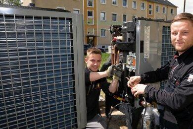 Frederic Göbel (r.) und sein Bruder Niclas Göbel von der Firma Elektroservice Hinkel aus Bermsgrün haben die Luftwärmepumpen vorm Haus verkabelt.