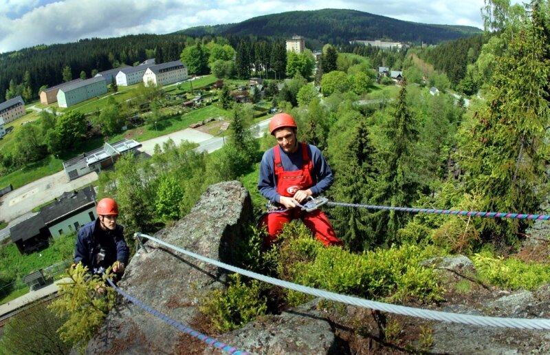 """<p class=""""artikelinhalt"""">Mitglieder des Outdoorteams Westerzgebirge, hier im Bild Jürgen Anger (l.) und Danny Kovacs, bauen eine Klettersteiganlage am Nonnenfelsen in Erlabrunn, oberhalb des Schwarzwassers. Damit soll das Angebot für Kletter-Touristen im Erzgebirge erweitert werden. </p>"""