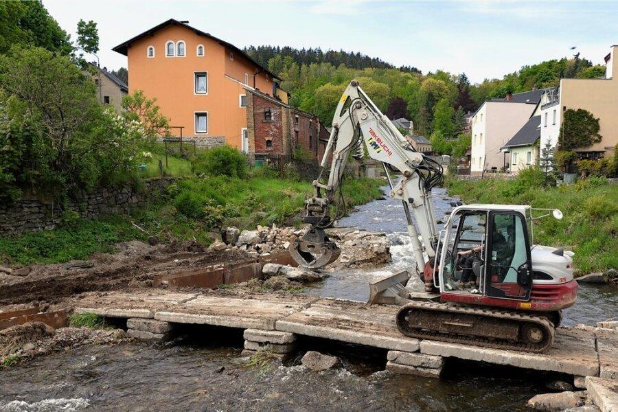 Für den kleinen Bagger, der den Abriss vornimmt, wurde ein provisorischer Betonsteg in den Flusslauf gebaut.