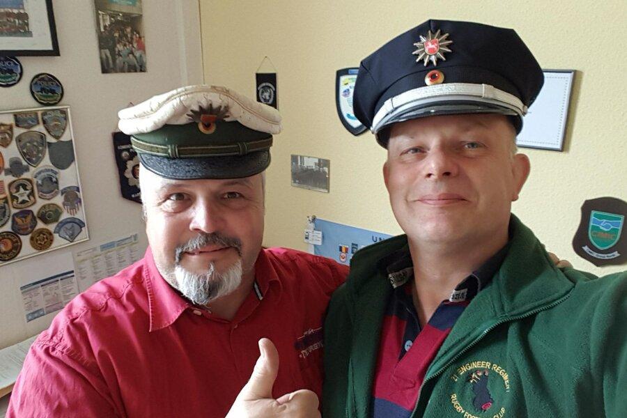 Rückkehr einer Mütze: Polizeioberkommissar Gabor Balint (links) - mit einer vor 37 Jahren gestohlenen Polizeimütze - und der Überbringer Graham Morley machen ein gemeinsames Foto.