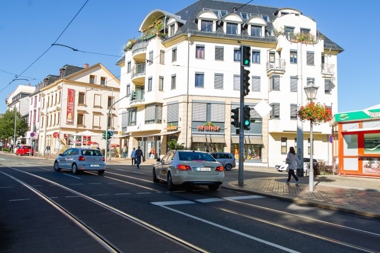 Eine kaputte Straße, halbhohe Baracken, graue Häuser - das prägte das Bild der Wilhelm-Pieck-Straße in Plauen in Höhe Theaterstraße. Die heutige Neundorfer Straße hat sich seit ihrer Sanierung 2008/09 als Geschäftsmeile behauptet. Ein prächtiges Geschäfts- und Ärztehaus ist entstanden - nicht nur wie hier im Bild rechts der Straße, sondern ein weiteres auch gegenüber am heutigen Hans-Löwel-Platz.