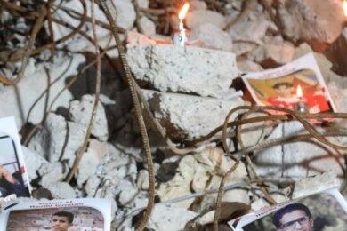 Fotos und Kerzen erinnern an Opfer des Bürgerkrieges im Jemen. Von einem Haus sind nach einem Angriff nur noch die Trümmer zu sehen, Menschen starben.