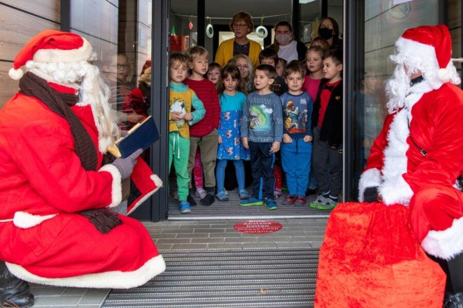 """Wie hier in der Peniger Kita """"Abenteuerland"""" haben die beiden Weihnachtsmänner Marco Steinbach und Mike Tauchmann (v. l.) auch in fünf weiteren Einrichtungen die Kinder mit Süßigkeiten überrascht."""