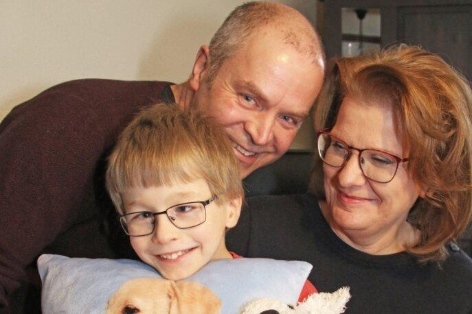 Gruppenbild mit Gurke: Die Pflegeeltern Heike und Sylvio Weigel freuen sich gemeinsam mit Felix darüber, dass der Assistenzhund bald nicht nur als Foto auf dem Kissen bei ihnen sein wird.