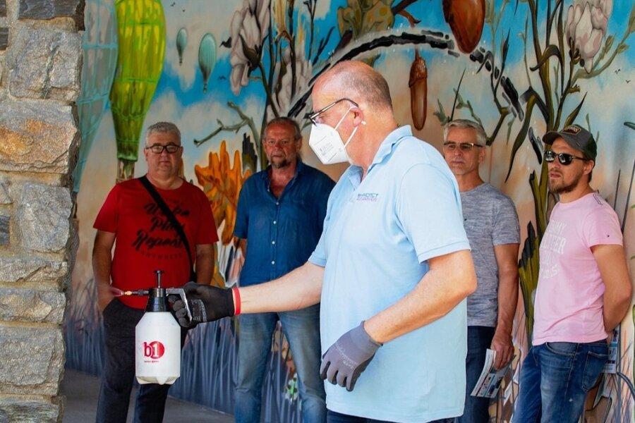 Graffiti-Schutz: Bernd Tank (vorn) führte an verschieden Materialien wie Beton, Metall, Putz und Naturstein im Stadtgebiet vor, wie nachhaltiger Graffitischutz funktionieren kann. Lediglich ein Wasserstrahl ist dann noch notwendig, um beschmierte Wände abzuwaschen, die im Vorfeld mit der Schutzschicht ausgestattet wurden. Frank Zabel (hinten links) und Mitarbeiter des städtischen Bauhofes informierten sich über die Methode.