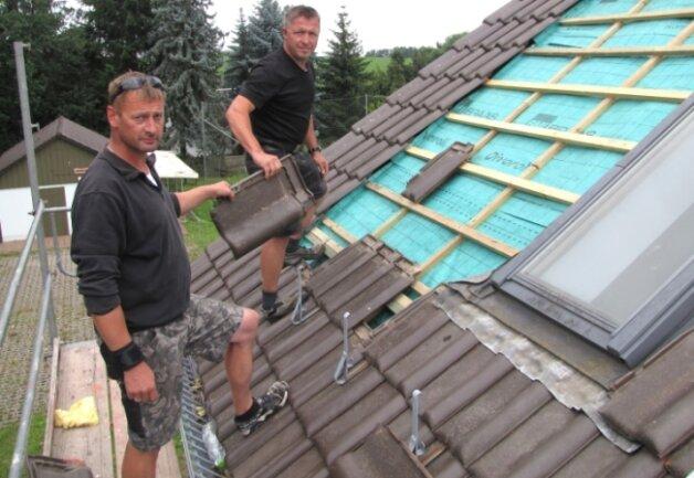 Roger Schroth (vorn) und Daniel Grießhammer von der Rochlitzer Dachdeckergenossenschaft werden noch in dieser Woche das Dach des Hermsdorfer Feuerwehrdepots abgedichtet haben.
