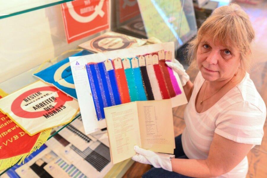 Museumsmitarbeiterin Ina Goldhardt hat früher selber im VEB Vogtlandstoffe in Treuen gearbeitet. Hier präsentiert sie eine Musterkarte, eine Arbeitsanweisung und Wimpel für ausgezeichnete Kollektive.