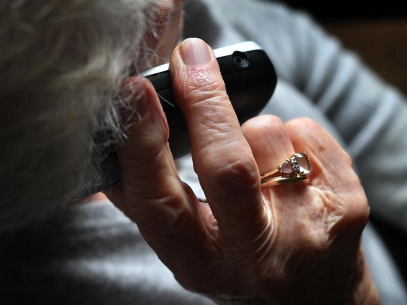 Eine Rentnerin hält ein Telefon in der Hand.