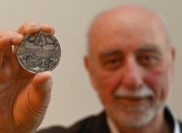 Helmut Herholz, Vorsitzender der Freiberger Münzfreunde, präsentiert die Medaille zum Schneeberger Stadtjubiläum.