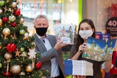 Peter Kober, Chef des Dachverbands Stadtmarketing, und Illustratorin Sarah Pilz freuen sich über das Plauener Wimmelbuch.
