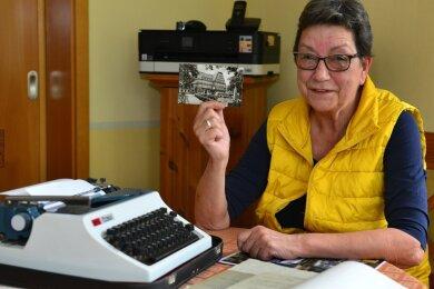 """Petra Schumann aus Hainichen hat von 1983 bis 2019 für die """"Freie Presse"""" gearbeitet. Ihre Texte hatte sie in den Anfangsjahren auf dieser Schreibmaschine verfasst. Das Foto in ihrer Hand zeigt den Sitz der Lokalredaktion im Stadthaus."""