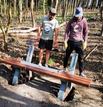 Sohn und Schwiegersohn beimAufstellen der Bank am Waldrand.