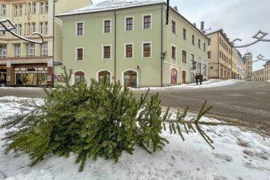 Ein ausrangierter Weihnachtsbaum in Annaberg-Buchholz liegt auf einem Fußweg. In Kürze startet die Sammeltour des Entsorgers. Dabei gibt es für jeden Ort einen festen Tag.