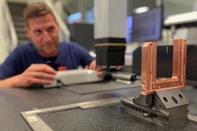 Jens Melzer, Mitarbeiter in der Qualitätssicherung, beim Vermessen eines Kühlkörpers für die Lasertechnik. Das Bauteil besteht aus Kupfer.