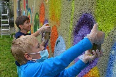 Leonard arbeitet am Dienstag zum ersten Mal überhaupt mit der Spraydose. Dem Achtjährigen hat es gefallen, die Wand bunt zu gestalten.