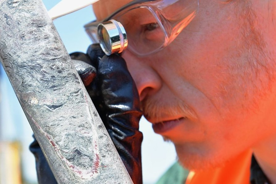 Jörg Neßler untersucht einen Bohrkern. Die rötliche Färbung im Glimmerschiefer ist Hämatit (Eisenoxid).