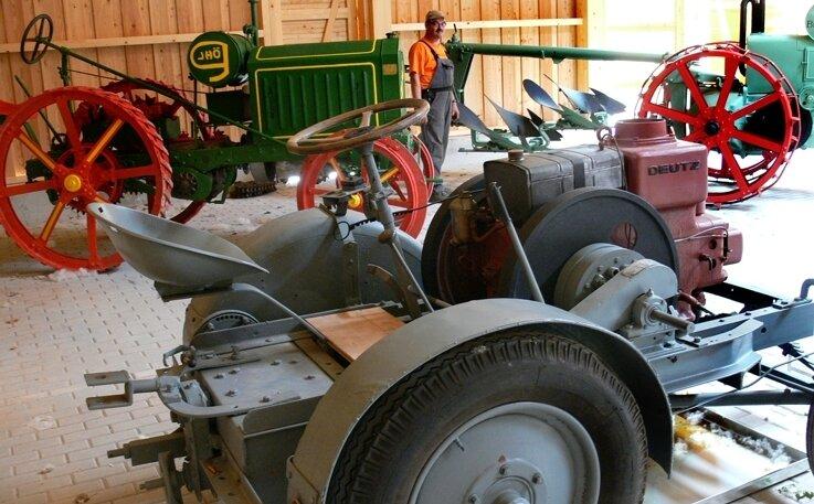 Die ersten Trecker stehen in der neuen Traktorenhalle. Museumsmitarbeiter Fred Flämig kümmert sich um die Fahrzeuge.