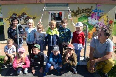Die Kinder vom Spatzennest in Trieb halfen Künstler André Wolf beim Bemalen der Fassade. Auch Kita-Leiterin Sandra Ebersbach freut sich über die neue Gestaltung.