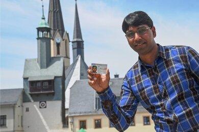 Der Pakistaner Muhammad Akram zeigt seinen Pass, der ihm ein Bleiberecht für drei Jahre in Deutschland gewährt. Der Bäckereigehilfe, vor der Bäckerei und der Stadtkirche in Burgstädt, sollte abgeschoben werden.