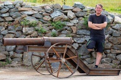 Michael Ebert und seine neueste Kreation: Die Kanonen-Attrappe vor der Naturstein-Mauer ist eine 470 Kilogramm schwere Garten-Deko.