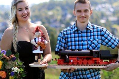 Julia Heilmann und Maximilian Hähnel zeigen ihre Gesellenstücke - einen rauchenden Dudelsackspieler und eine Eisenbahnlok. Sie sind zwei von insgesamt 13 neuen Holzspielzeugmachern, die nun in Seiffen freigesprochen wurden.