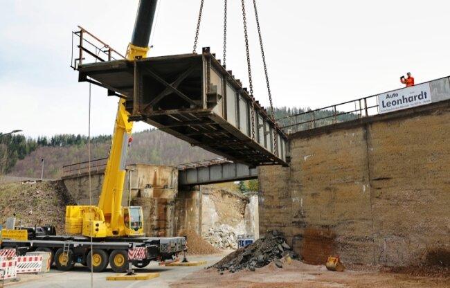 Kurz nach 10 Uhr schwebt der erste Metallträger der alten Eisenbahnbrücke zu Boden. Für 6,5 Millionen Euro will die Erzgebirgsbahn eine neue, schlanke Gleisbrückenkonstruktion errichten.