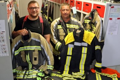 Gemeindewehrleiter Rico Leuschner (links) zeigt eine der alten Jacken, Ortswehrleiter Sven Weinhold die neue Ausrüstung.