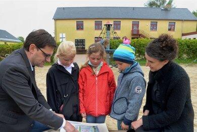 Schulleiterin Sandra Forycki (rechts) und Bürgermeister Andreas Gruner (links) zeigen Merle, Ella und Jonathan, wie die Freiflächen an der Grundschule Rothenkirchen umgestaltet werden sollen. Neben Sportanlagen ist ein neuer Spielplatz geplant.