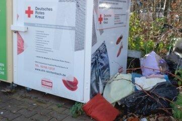 Neben dem DRK-Kleidercontainer an der Rosa-Luxemburg-Straße in Reichenbach liegen alte Klamotten, Handtücher, Hausschuhe und ein kaputter Bildschirm.