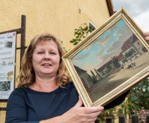 Manuela Neuhaus vom Heimatverein Wechselburg zeigt ein Original des Malers Leuteritz.