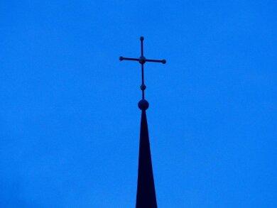Ein Kreuz ist an einer Kirchturmspitze zu sehen.