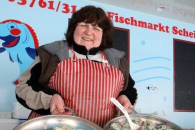 Fischverkäuferin Marion Kreissl ist eigentlich abgehärtet. Trotzdem hat sie sich dick angezogen. Ein Heizer hinter der Theke bringt zusätzlich Wärme.